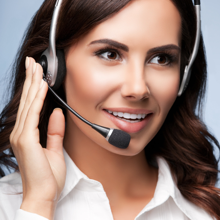 one person: Portrait of cheerful customer support female phone operator in headset, over grey background. Consulting and assistance service call center.