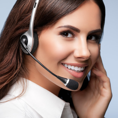 Support: customer support phone operator in headset, against grey background. Consulting and assistance service call center.