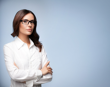 business attire teacher: Portrait of seriously looking young businesswoman in glasses, with blank copyspace area for slogan or text message, over grey background Stock Photo