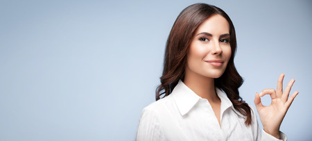 allright: Portrait of happy smiling young cheerful businesswoman, showing okay hand sign gesture, with blank copyspace area for slogan or text message, over grey background