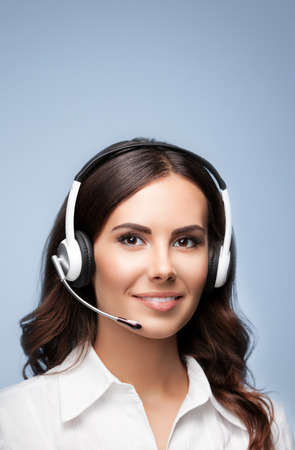 handsfree phone: Female customer support phone operator in headset, with blank copyspace area for slogan or text message, over grey background