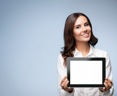 showing: Portrait of cheerful beautiful young brunette businesswoman showing blank no-name tablet pc monitor, over grey background, with copyspace area for slogan or text message