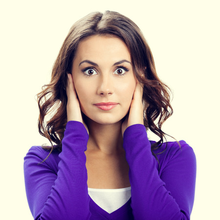 hands covering ears: Portrait of young woman covering with hands her ears, in violet casual clothing Stock Photo
