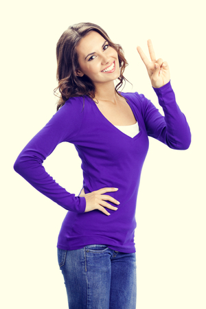 2 persons only: Happy smiling beautiful young woman showing two fingers or victory gesture, in violet casual clothing Stock Photo