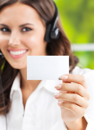 debet: Portrait of happy smiling cheerful beautiful young support phone operator in headset, showing blank business or plastic card with copyspace, focus on card Stock Photo