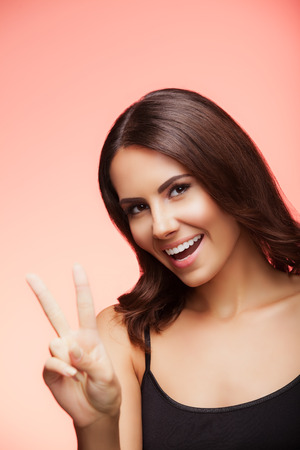 2 persons only: Portrait of beautiful young woman showing two fingers or victory gesture, on light red background Stock Photo