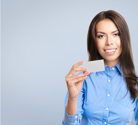debet: Happy smiling business woman showing blank business or credit card, against grey backround Stock Photo