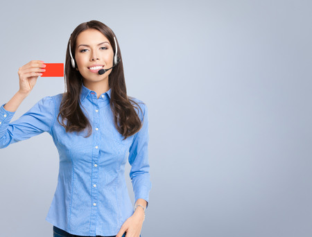 debet: Portrait of smiling cheerful customer support phone operator in headset, showing red blank business or plastic card, against grey background Stock Photo