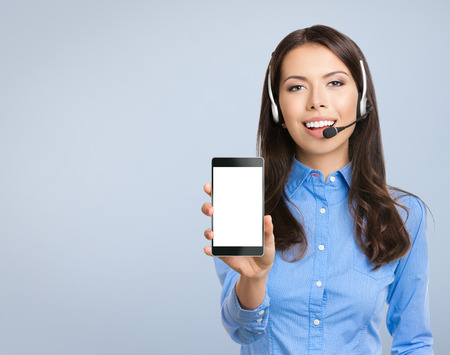 blank center: Happy smiling beautiful young customer support phone operator showing blank no-name cellphone, against grey background