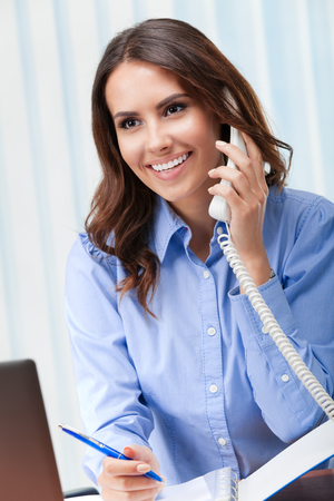 one person: Portrait of happy smiling cheerful beautiful young business woman or support phone worker, at office Stock Photo