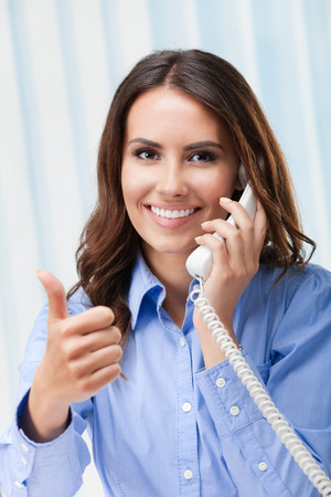 business support: Portrait of happy smiling cheerful beautiful young business woman or support phone worker with thumb up geture, at office
