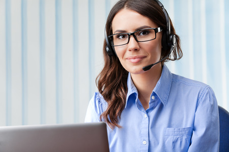Portrait of happy smiling cheerful beautiful young support phone operator in headset, at office