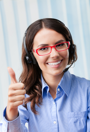 handsign: Portrait of happy smiling cheerful young support phone operator in headset, showing thumbs up gesture, at office