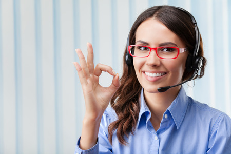handsign: Portrait of happy smiling cheerful young support phone operator in headset, showing okay gesture, at office Stock Photo