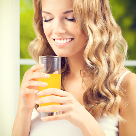 blonde woman: Portrait of happy smiling young beautiful woman drinking orange juice, square composition