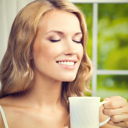 tomando café: Retrato de joven feliz sonrisa del café Mujer de consumición o té, en el hogar, composición de la plaza
