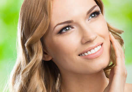 blondy: Portrait of happy smiling young lovely woman touching skin or applying cream, outdoors