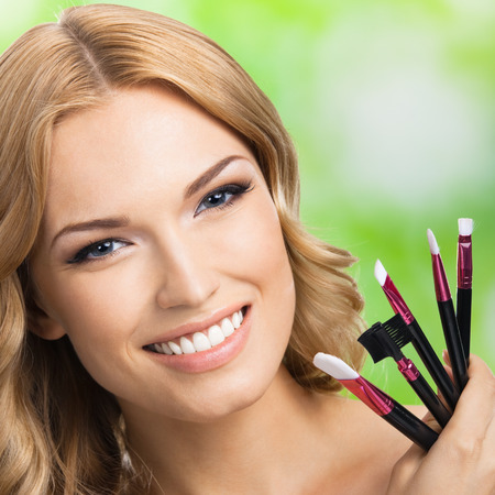 summer beauty: Portrait of young happy smiling blond lovely woman with make up tools, outdoors