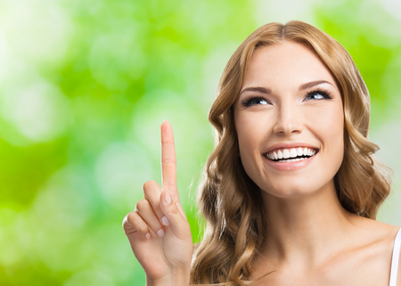 cheerful: Young happy smiling blond lovely woman, showing up, one finger or idea gesture, outdoors