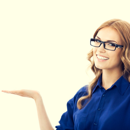 looking at camera: Portrait of smiling beautiful young businesswoman in blue clothing showing something or blank copyspace area for slogan or text message Stock Photo
