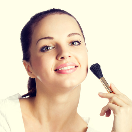 covering face: Young happy smiling woman with cosmetics brush