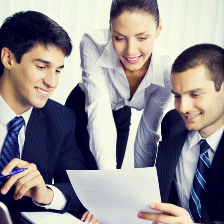 trabajo en equipo: Tres jóvenes empresarios que trabajan con el documento en la oficina, trabajo en equipo concepto
