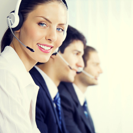 customer service: Three smiling young customer support phone operators at workplace, customer service concept