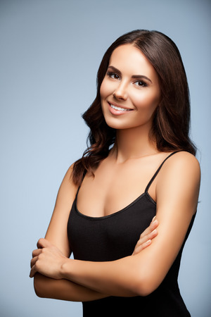 top clothing: portrait of thinking young woman in black tank top clothing, on grey background Stock Photo