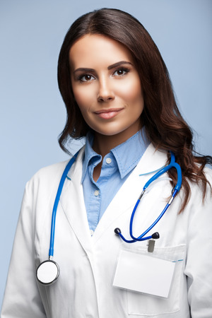 serious doctor: Portrait of happy smiling young female doctor, on grey background