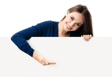 showing: Portrait of happy smiling young woman in blue casual smart clothing, showing empty blank signboard with copyspace area for text or slogan, isolated against white background Stock Photo