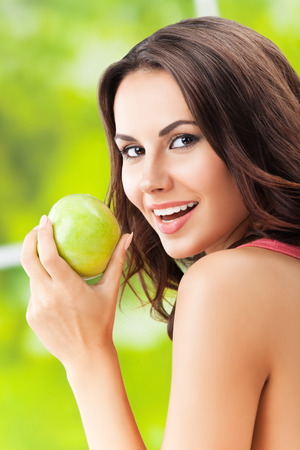 eating fruits: Young happy smiling woman with green apple