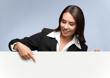 advertising woman: Portrait of happy smiling young businesswoman in black suit, showing blank signboard with blank copyspace area for slogan or text, over grey background