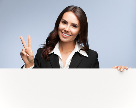 women business: Portrait of happy smiling young businesswoman in black suit, showing blank signboard with blank copyspace area for slogan or text, over grey background, showing two fingers or victiory gesture
