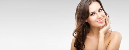 Portrait der schönen jungen Frau mit langen lockigen Haaren, über grauem Hintergrund, mit Copyspace Standard-Bild - 48289245