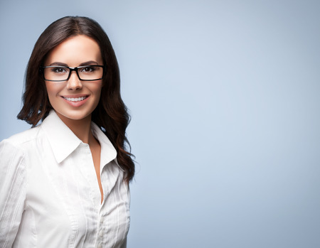 Portrait of smiling young cheerful brunette businesswoman in glasses, over grey background, with copyspace