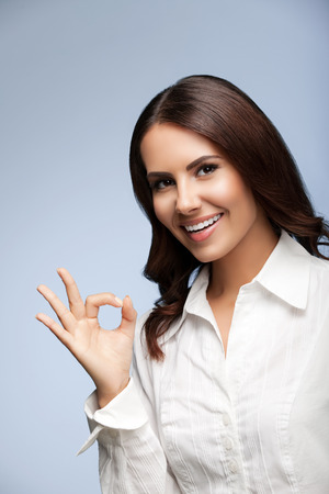 allright: Portrait of happy smiling young cheerful businesswoman, showing okay hand sign gesture Stock Photo