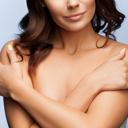 undressed woman: closeup of woman with arms crossed on her chest, naked shoulders, on grey background Stock Photo