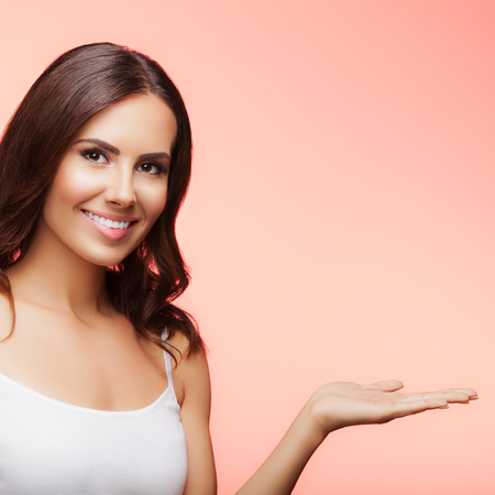 copyspace: Portrait of cheerful smiling young woman showing copyspace or something, over blue background Stock Photo