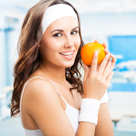 alimentos saludables: Retrato de feliz sonriente mujer hermosa con naranja, en el gimnasio o en el gimnasio