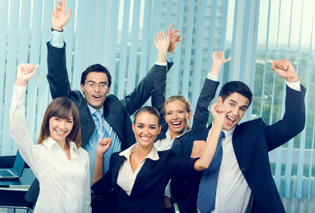 Corporations: Happy successful gesturing business team at office Stock Photo