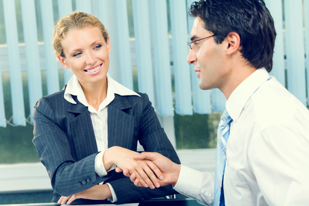 flattery: Two businesspeople cheering by handshake or flirting at office Stock Photo