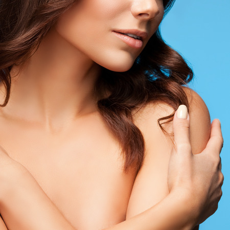 donna completamente nuda: Primo piano di donna con le braccia incrociate sul petto, spalle nude e gli occhi chiusi, su sfondo blu Archivio Fotografico
