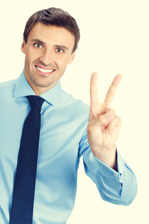 2 persons only: Happy smiling young business man showing two fingers or victory gesture