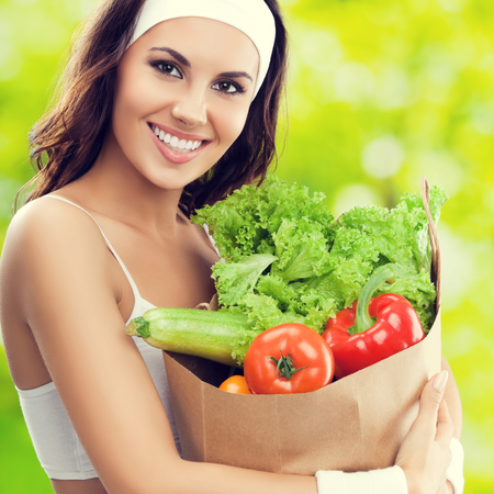 Happy smiling young lovely brunette woman in fitness wear holding grocery shopping bag with healthy vegetarian raw food, outdoors. Healthy lifestyle, beauty and dieting concept.