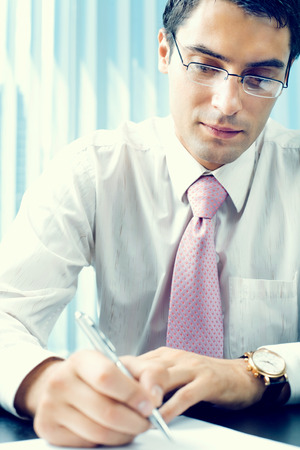 consulting business: Writing businessman with documents at office