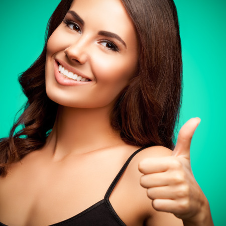 top clothing: Portrait of beautiful cheerful smiling young woman in black tank top clothing, showing thumb up gesture, on green background