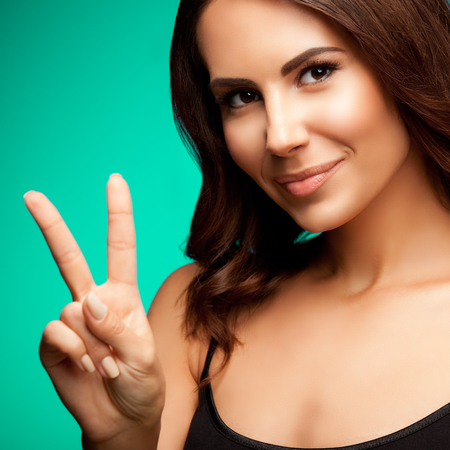 fingers on top: Beautiful young woman in black tank top clothing, showing two fingers or victory gesture, on green background Stock Photo