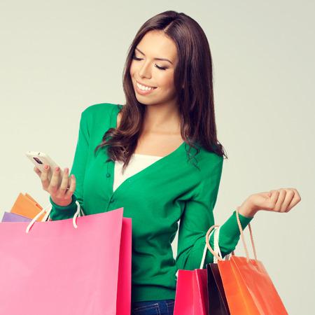 chicas de compras: Retrato de joven feliz sonriente mujer encantadora con bolsas de la compra, con copyspace área vacía en blanco para el texto o lema, llamando por teléfono celular
