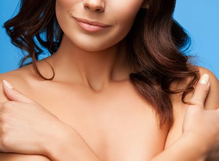 mujer sexy desnuda: Mujer con los brazos cruzados sobre el pecho, los hombros desnudos sobre fondo azul
