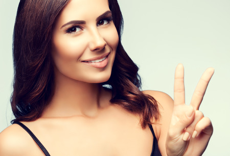 fingers on top: woman in black tank top clothing, showing two fingers or victory gesture Stock Photo